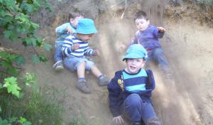 Kinder rutschen den Hang herunter